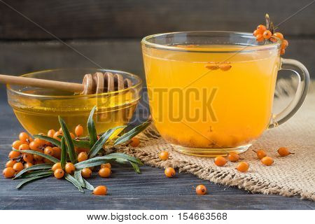 Tea of sea-buckthorn berries with a sprig on sackcloth and a wooden background.