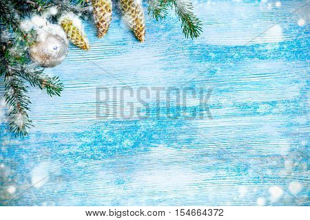 Christmas decorative background. Fir tree branch covered with snow, fir decorated with pine cones and Christmas balls. on a blue wooden background.