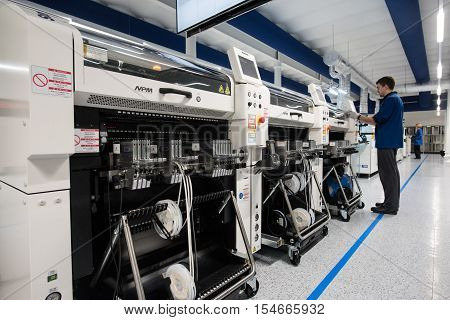 Saint-Petersburg Russia - November 2 2016: Manufacturer of automotive security systems Starline. Young male operator in the production line of chips. In the foreground machine with chips.