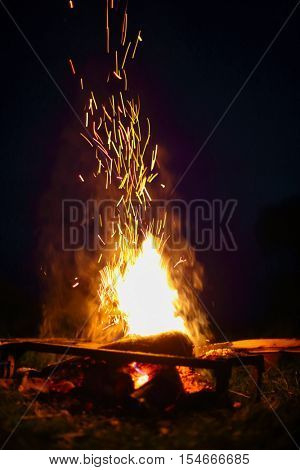 Bright warm fire with sparks at night at nature during walking-tour