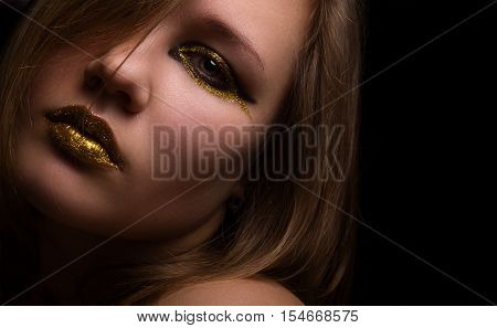 Young beautiful woman with black and gold eyeliner make-up looking at camera. Close up.