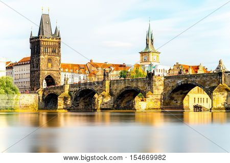 Citycsape view on the riverside with the bridge and old town in Prague. Long exposure image technic with glossy water