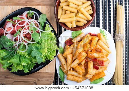 Top View Of Cooked Rigatoni Pasta And Fresh Salad