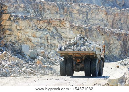 Huge dump truck transporting granite rock or iron ore