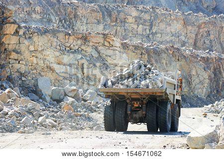 Huge dump truck transporting granite rock or iron ore