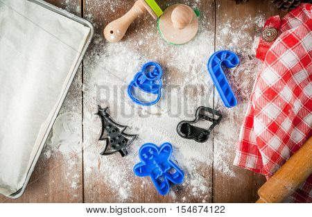 Making cookies for Christmas and New Year. Fun food for kids, a snack for a party. On wooden table pan with unbaked cookies, cookie cutters, rolling pin, flour, towel