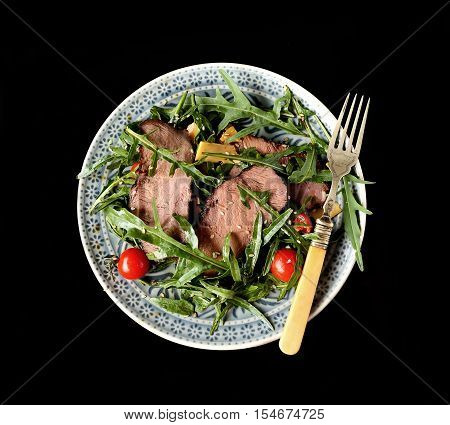 salad of arugula and roast beef on a black background