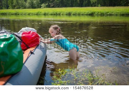 Little girl in swimsuit pushes inflatable boat in river during camping trip at summer