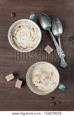 Two cups of coffee and are several pieces of sugar and teaspoons; top view flat lay