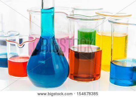 volumetric flask and various beakers with different types of indicators in acids and basis four colors of indicators in several solusions