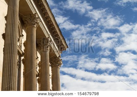 Horizontal photo of classical building columns with blue sky and clouds
