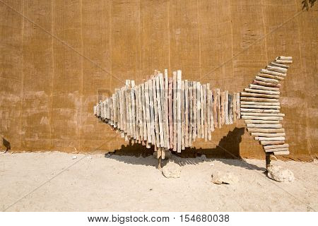 MUHARRAQ, BAHRAIN - OCT 29, 2016: Directional sign board made of wooden poles in the shape of a fish in the Bu Maher Fort in Arad.