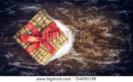 Christmas gift swept snow on a wooden background.