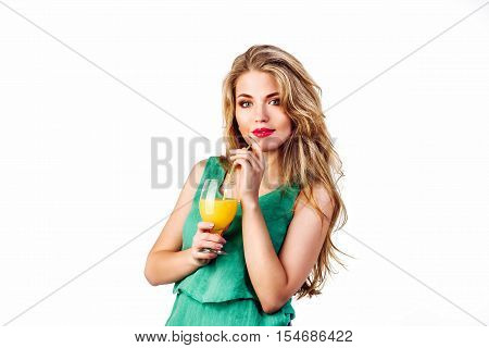 Pretty young beautiful woman drinking orange juice . Girl in green dress hold slass of juice on white background