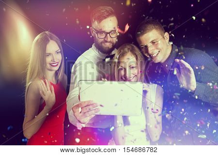 Group of young friends having fun at New Year's Eve party and making a midnight video call to friends and family