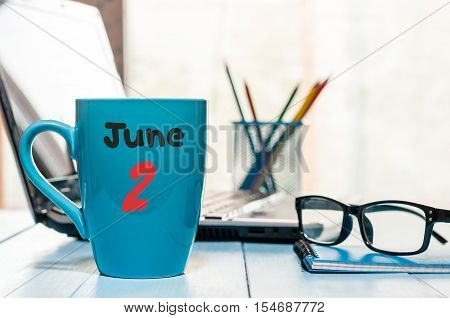 June 2nd. Day of the month 2 , color calendar on morning coffee cup at business workplace background. Summer concept. Empty space for text.
