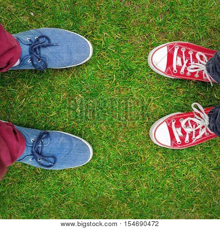 Red and Blue Sneakers shoes walking on grass concrete top view Canvas shoes walking on concrete two sneakers behind each others as a sign of love Sneakers shoes Couple