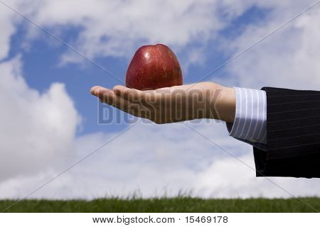 a businessman hand holding an apple, as symbol of business temptation