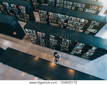 Overhead view of young woman looking for a book in shelf. University student in library selecting a book.