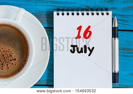 July 16th. Day 16 of month, calendar on business workplace background with morning coffee cup. Summer concept. Empty space for text.