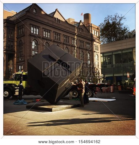 NEW YORK - NOV 1: NYC employees re-install the Alamo sculpture at Astor Place on Nov 1, 2016 in New York City. The sculpture was created by artist Tony Rosenthal and first installed in 1967.