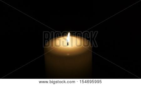 burning candle isolated on a black background