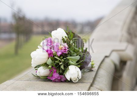 Romantic wedding fresh colorful bouquet on stone handrail in a daylight on the background of park with green grass