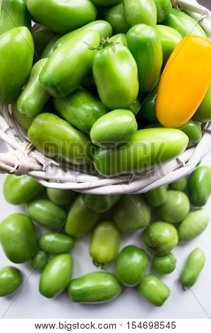 Young green tomatoes in a basket on white