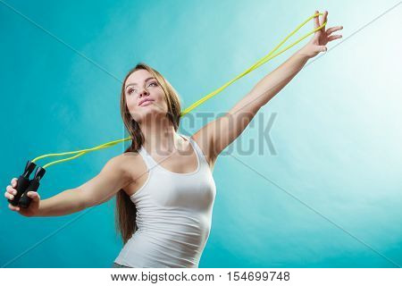Young fit slim woman spend actively free time. Beauty happy girl wearing sports clothes with jumping skipping rope on blue background.