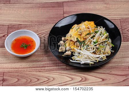 Thai food.,Fried egg and oyster with bean sprouts and shallot as Hoi Tod Khai in Thai served with chili sauce.