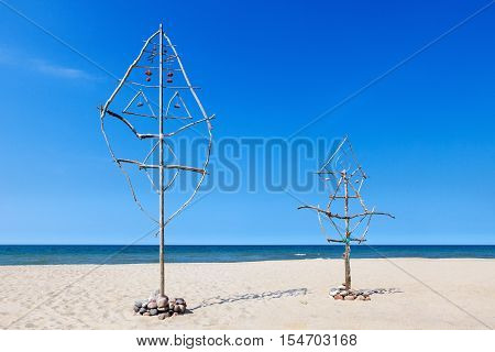 large Dream catcher made of sticks and stones on the beach by the sea
