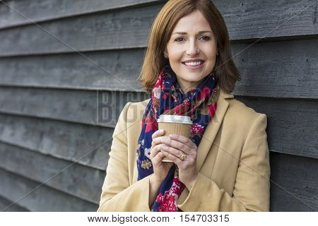 Portrait shot of an attractive, successful and happy middle aged woman female outside drinking coffee in a disposable takeaway cup.