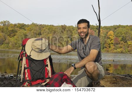 Young man with backpacking equipment outdoors with fall trees in background