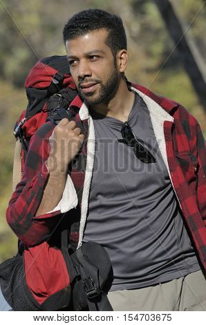 An outdoor portrait of hispanic man backpacking in the woods