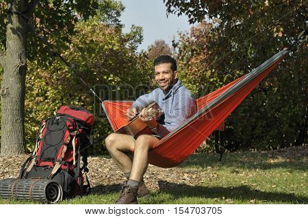 Young Hispanic man playing guitar in a hammock on vacation