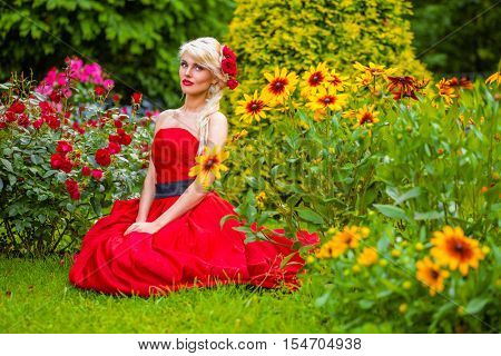 half length portrait of beautiful woman in red dress in summer park sitting on grass among flower beds