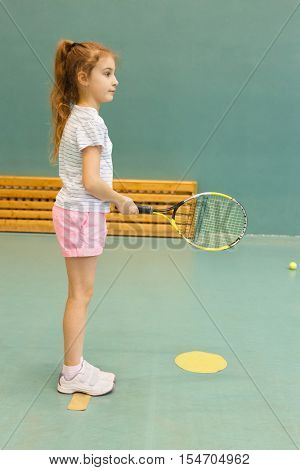 young female tennis player on tennis court holding racquet, in gym
