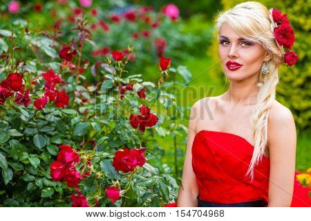 half length portrait of beautiful woman in red dress in summer park sitting on grass and looking at camera