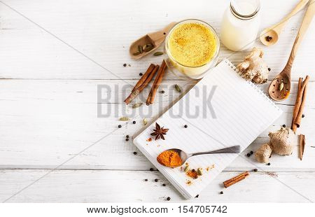 Golden turmeric latte in a glass spices and recipe book over white wooden background with copy space
