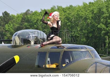 Sexy Christmas pinup holding up a mistletoe and blowing a kiss while sitting on top of a WWII bomber aircraft