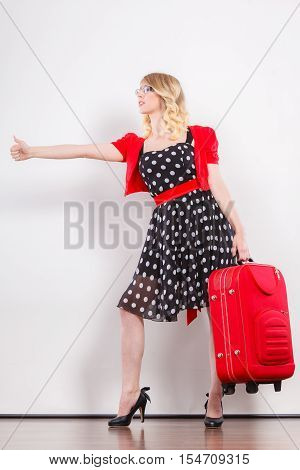 Traveling vacation ew life concept. Elegant lovely woman wearing polka dot black dress with red suitcase ready for trip journey hitchhiking giving thumb up