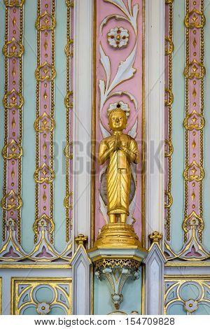 The golden budha on the wall at thai temple.