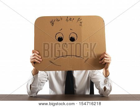 Businessman in the office holds a cardboard with a sad face