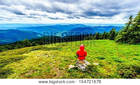 Senior Woman enjoying the View of the Shuswap Highlands in central British Columbia on a Cold and Windy Day