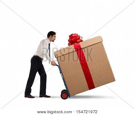 Businessman pushes heavy great gift with a cart