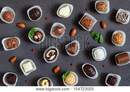 Sweet food pattern: assortment of chocolate pralines, nuts, candies and bonbons. Top view