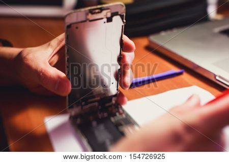 A close-up process of disassemble and dismantle modern mobile phone smartphone with broken shattered display glass and changing details at home