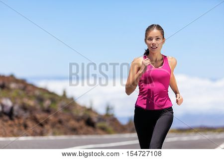 Fit sport athlete running woman runner jogging outdoor on road training for marathon race run. Asian young woman running outdoors working out cardio. Beautiful fit fitness model in her 20s.