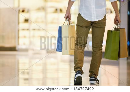Rear view of young man carrying many shopping bags