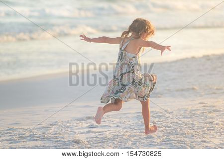 Litle girl with braided hair and nice dress running on sand on the beach pretending to fly in sunset